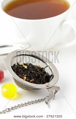 tea strainer with a fragrant black tea and cup in the background