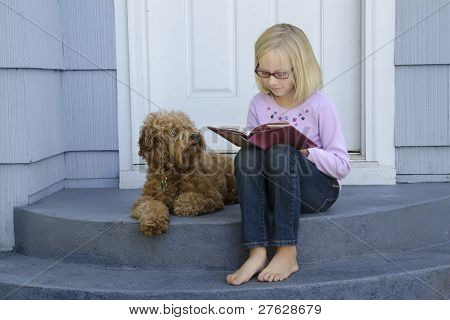 Young Girl Reading With Dog At Side
