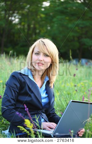 Businesswoman On Grass With Laptop