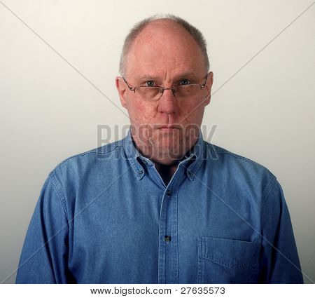 Older Man In Blue Denim Shirt And Glasses Looking Glum