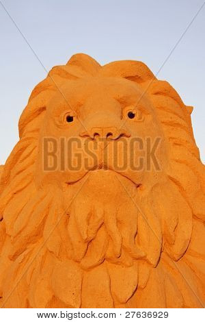 Lion made from sand against a blue sky