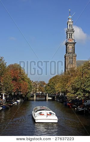 Westerkerk and canal with cruiseboat in Amsterdam the Netherlands