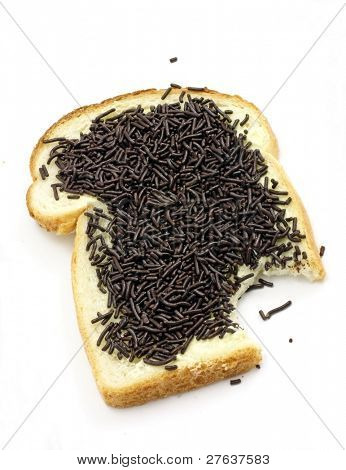 A slice of white bread with chocolate sprinkles, a typical dutch breakfast, isolated on white