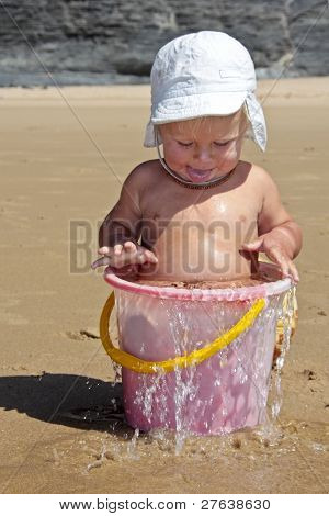 Cute little baby boy playing in a bucket full of water at the beach
