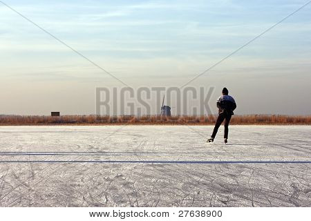 Lonely ice skater on a cold winter in the countryside on frozen ice in the Netherlands