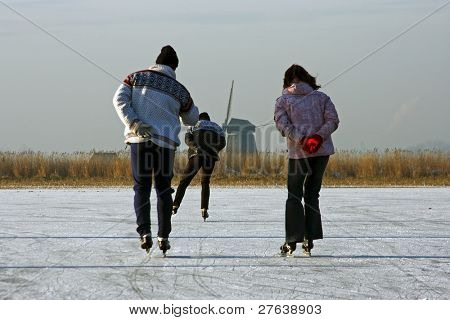 Ice skating on a cold winterday in the countryside on a frozen lake  in the Netherlands
