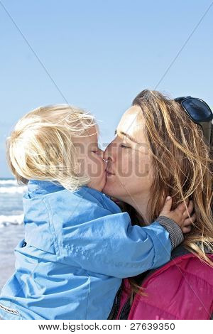 Mamma and little boy cuddling and hugging at  the beach