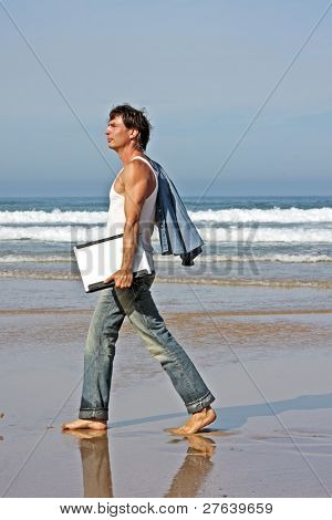 Young guy walking with his laptop on the beach