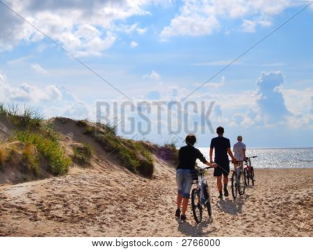 Three Persons With Bicycle  Go To Seacoast