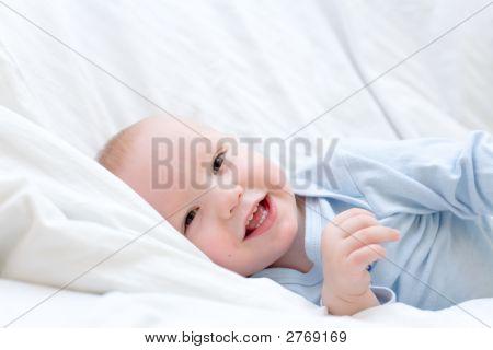 Little Joyful Baby Resting On White Bed