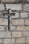 High resolution conceptual Christian cross over an old stone wall ideal for religious or faith desig