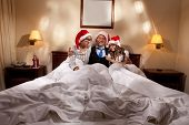 image of promiscuous  - Manager with two his subordinates reading a business plan sitting in bed on New Year - JPG