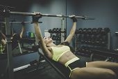 Side View To Sporty And Fit Beautiful Woman Exercising With Barbell At Gym Background. Smiling Girl  poster