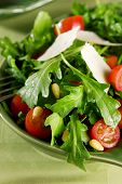 stock photo of pine nut  - Arugula tomato salad with pine nuts and parmesan cheese - JPG