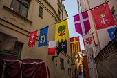 Flags Hanging On The Street Rozena Iela. Narrow Street In Old Town Riga, Latvia With Stars Garland.  poster