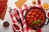 Meatballs In Tomato Sauce With Spices In A Frying Pan And Cherry Tomatoes On A Cutting Board And Whi poster