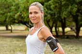 Portrait of athletic mature woman resting after jogging. Beautiful mid blonde woman running at park  poster