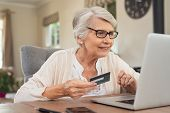 Happy senior woman making online payments using laptop. Smiling old grandmother doing shopping on ec poster