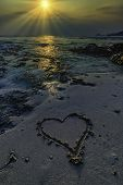 Romantic View Of Heart Shape In Sand With Sunset Background poster