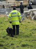 stock photo of truncheon  - Uk police officers with a police dog at the scene of a public disturbance - JPG