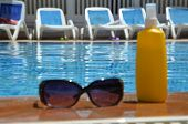 Sunglasses And Yellow Sunscreen Near A Blue Pool Outside. Concept Of Vacation, Vacation, Summer At T poster