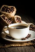 Coffee Cup And Beans On A Rustic Background. Coffee Espresso And A Piece Of Cake With A Curl. Cup Of poster