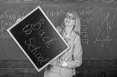 Hiring Teachers For New School Year. Woman Teacher Holds Blackboard Inscription Back To School. Look poster