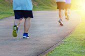 Fat Man Jogging, Catching Up With Thin Men. Low Angle View Of Runners Running In Park. Blurred Feet  poster