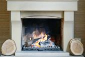 A Warm Fire In The Stone Fireplace On A Cold Night. Warm Cozy Fireplace With Real Wood Burning In It poster