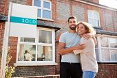 Portrait Of Excited Couple Standing Outside New Home With Sold Sign poster