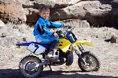 foto of moto-x  - Horizontal image of a young boy motor cross racer sitting on a yellow dirt bike in the desert against a formation of lava rim rock.