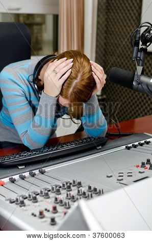 Portrait Of Depressed Female Dj Working In Front Of A Microphone On The Radio