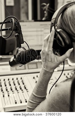 Rear View Of Female Dj Working In Front Of A Microphone On The Radio. Blach And White