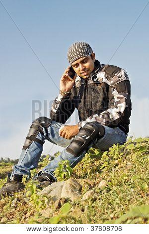 Man Sat At Roadside Using Cell Phone