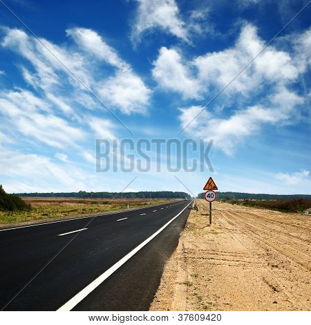 Long Asphalt Road And Blue Sky