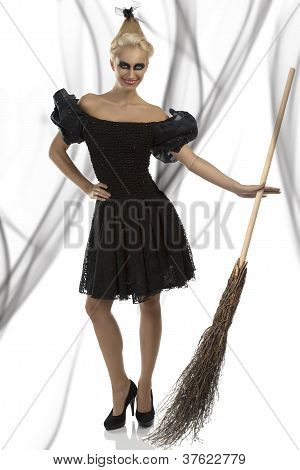 Sexy Girl In Halloween Suit With Besom Smiles