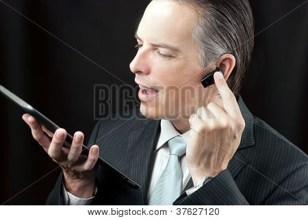 Businessman Using Tablet Adjusting Headset Earpiece.