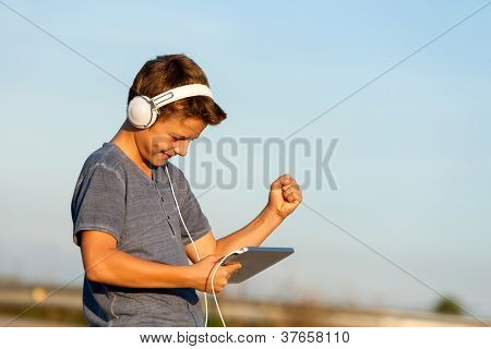 Happy Boy Listening To Music On Digital Tablet.