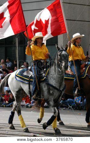 Jinetes de mujeres amarillo con banderas a caballo