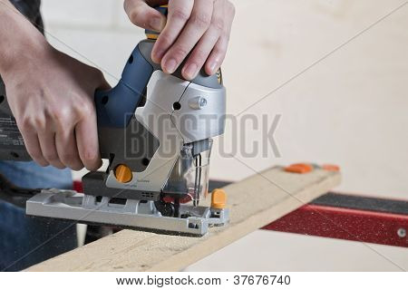 Man Cutting A Piece Of Wood