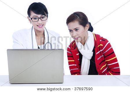 Doctor And Patient Looking At Laptop For Prescription