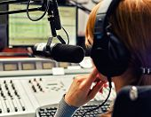 stock photo of mass media  - Rear view of female dj working in front of a microphone on the radio - JPG