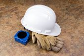 picture of osha  - A white hard hat with well used work gloves and blue tape measure on a mottled background - JPG