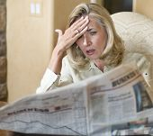 foto of stock market crash  - Mature woman reading financial newspaper about stock market crash - JPG