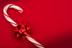 pic of candy cane border  - Candy cane with red bow on red background candy cane - JPG