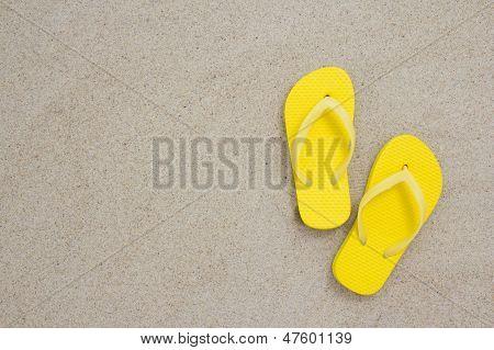 Flip-Flops amarelos deitada na areia