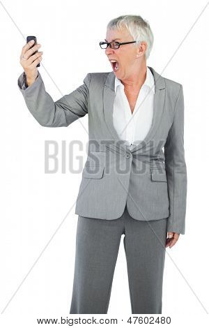 Furious businesswoman screaming during a call on white background