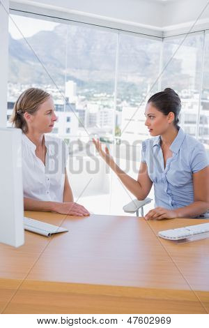 Businesswomen arguing in the office sitting at their desk