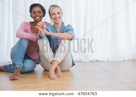Happy young housemates showing their new house keys and smiling at camera
