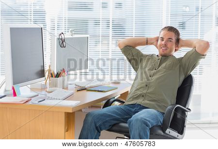 Smiling designer leaning back at his desk in a modern office